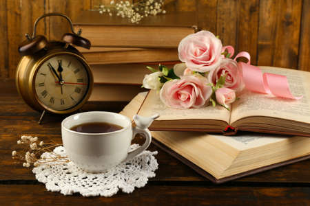flores secas: Taza de té con los libros y flores sobre fondo de madera