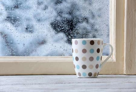 Cup of hot drink on windowsill on rain background Standard-Bild