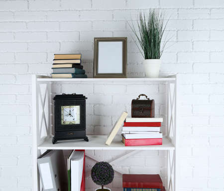 bookshelf: Bookshelves with books and decorative objects on brick wall background