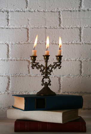 Bookshelf with books and candlestick on brick wall background photo