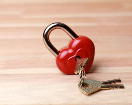 Heart-shaped padlock with key on wooden background photo