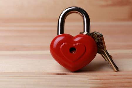 bibelot: Heart-shaped padlock with key on wooden background Stock Photo