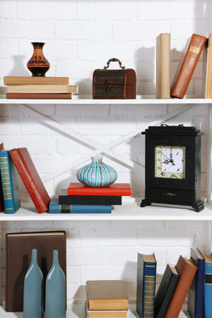 Bookshelves with books and decorative objects on brick wall background photo