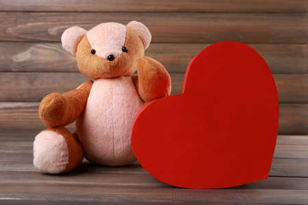 Teddy Bear with red heart on wooden background Stock Photo