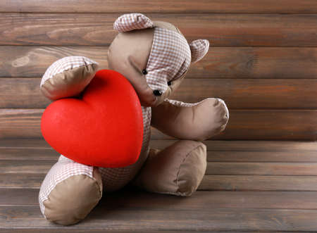 shame: Teddy Bear with red heart on wooden background Stock Photo