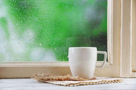 Kop van hete drank met servet op vensterbank op regen achtergrond Stockfoto