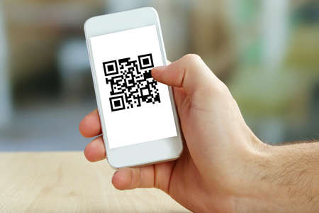 Hand holding smartphone with QR code on the screen Stockfoto