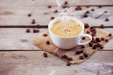 granos de cafe: Taza de caf� en la mesa de madera, de cerca