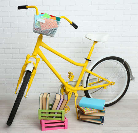 Bicycle with books in crate on brick wall background photo
