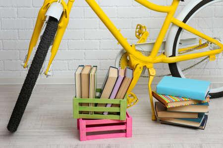 decorated bike: Bicycle with books in crate on brick wall background Stock Photo