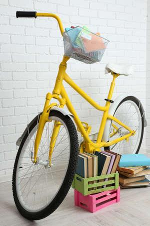 decorated bike: Bicicletta con libri in cassa sul muro di fondo