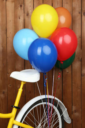 decorated bike: Yellow bicycle with balloons on wooden wall background