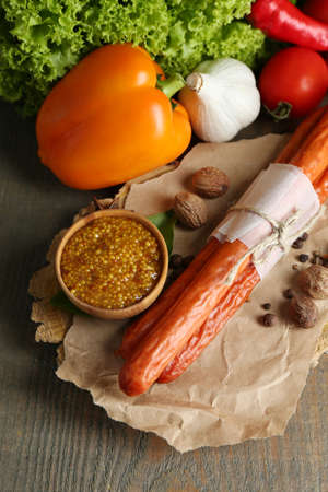 Composition of smoked thin sausages, mustard in bowl and spices on cutting board, on wooden background photo