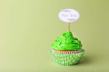 bake sale: Delicious cupcake with inscription on green background