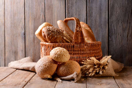wicker basket: Different bread on table on wooden background
