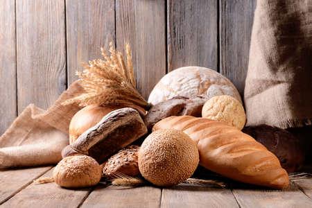 productos naturales: Diverso pan en la mesa sobre fondo de madera