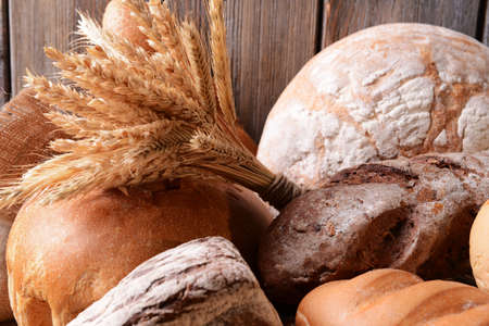 Different bread on table on wooden background photo