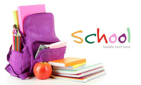 convivencia escolar: Mochila púrpura con útiles escolares aislados en blanco Foto de archivo