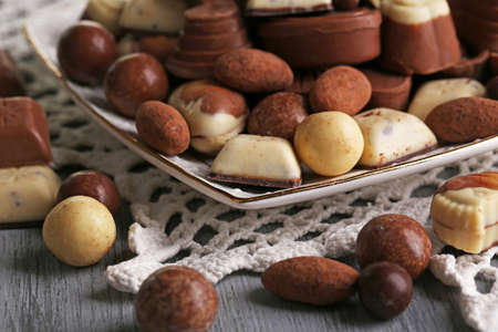 Different kinds of chocolates on plate on wooden table photo