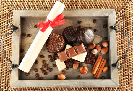 rolled paper: Sweets with rolled paper on wooden stand and wicker mat background