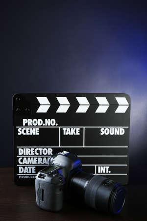 Photo camera and movie clapper on dark background photo