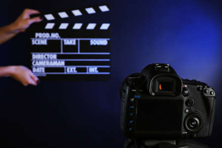 Hands with movie clapper board in front of camera on dark background photo