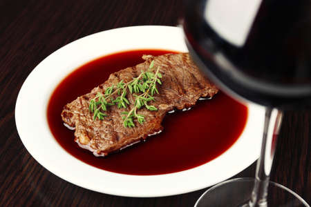 Glass of wine with steak on wooden background photo