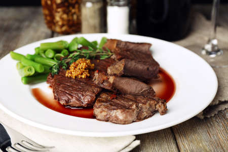 wine sauce: Steak with wine sauce on plate on wooden table
