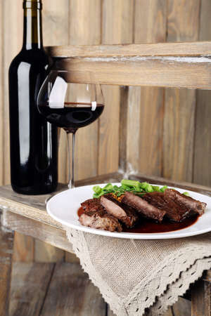 Steak with wine sauce on plate and bottle of wine on wooden background photo