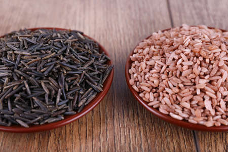 pales: Red and black rice in pales on wooden background
