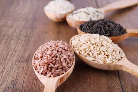 brown: Different kinds of rice in spoons on wooden background