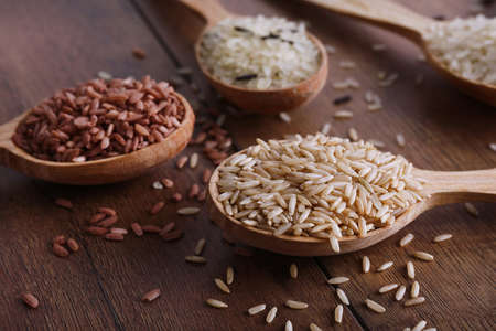 kinds: Different kinds of rice in spoons on wooden background