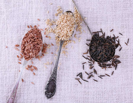 kinds: Different kinds of rice in spoons on fabric background
