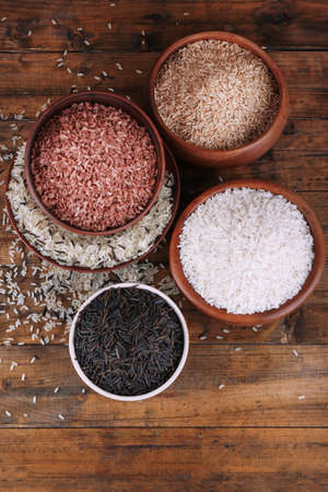 kinds: Different kinds of rice in bowls on wooden background