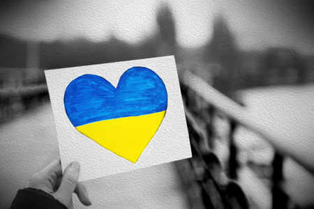 Hands holding paper heart with painted Ukraine flag photo