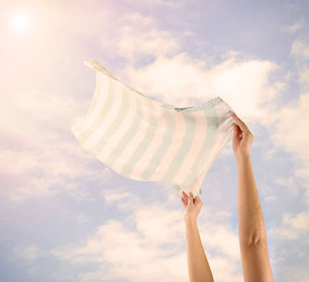 Hands holding flying shirt on sky background photo