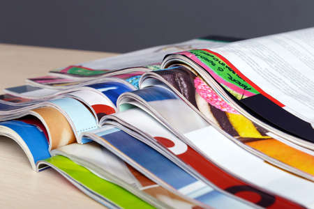 Magazines on wooden table on gray background Archivio Fotografico