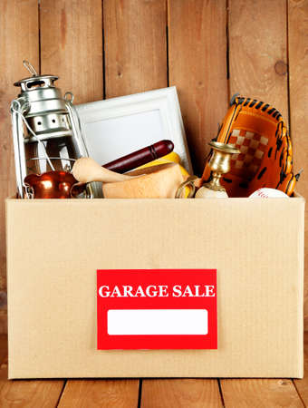 Box of unwanted stuff ready for a garage sale on wooden background Stock Photo