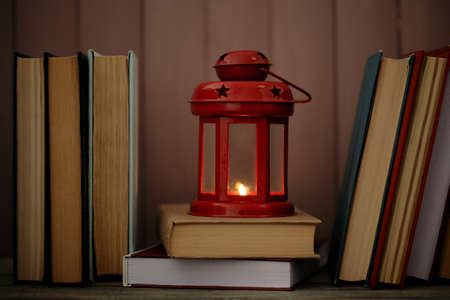 cosily: Books and decorative lantern on table and wooden planks background