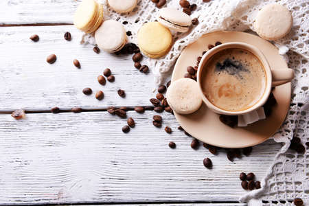 Gentle colorful macaroons and  coffee in mug on color wooden  background photo