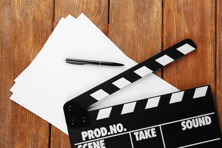 movie director: Movie clapper with sheets of paper and pen on wooden planks background