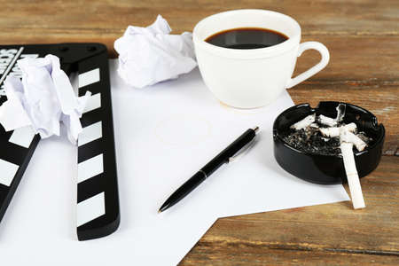 Movie clapper with cup of coffee and ashtray with cigarette butts photo