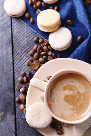 Gentle colorful macaroons and  coffee in mug on wooden table background, top view photo