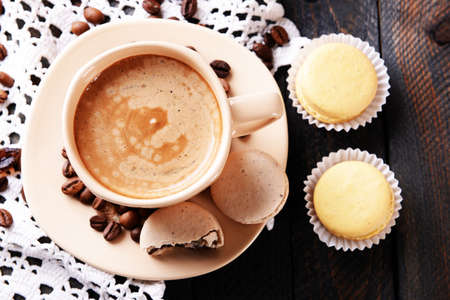 Gentle colorful macaroons and  coffee in mug on wooden table background photo