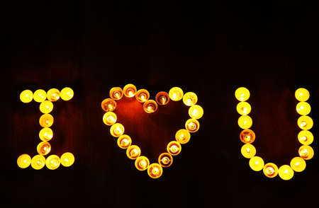 burning love: Words I LOVE YOU formed by burning candles on dark background