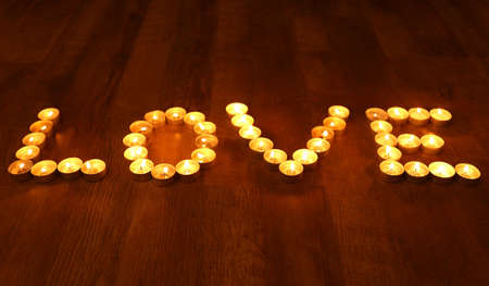 burning love: Word LOVE formed by burning candles on dark background