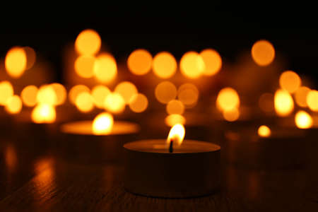 the memorial: Burning candles on dark background