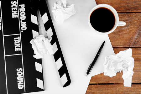 carta e penna: Movie clapper with paper, pen and cup of coffee on wooden planks background Archivio Fotografico