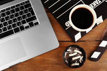 Movie clapper with laptop and cup of coffee on wooden background photo