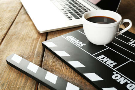 script: Movie clapper with laptop and cup of coffee on wooden background